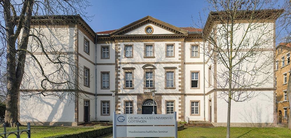 Weißes Gebäude mit einem Schild davor. Auf dem Schild steht Georg-August-Universität Göttingen Musikwissenschaftliches Seminar.