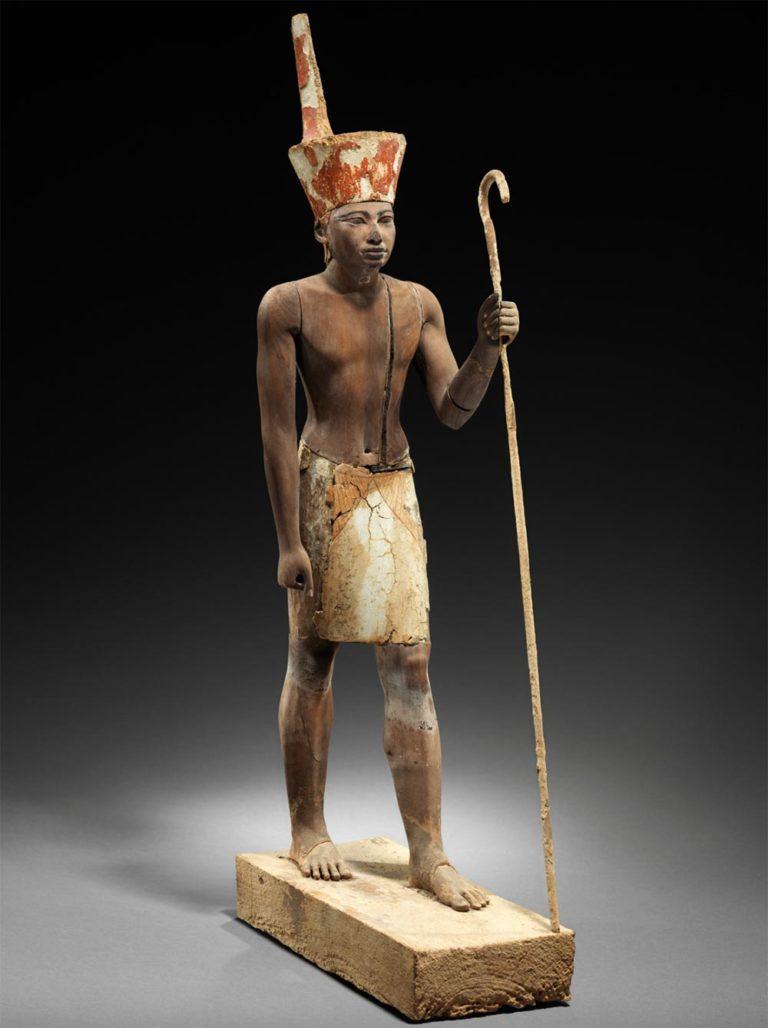 Hölzerne Statuette eines Pharao, in schreitender Schrittstellung, trägt einen Schurz und die rote Krone Unterägyptens, in der linken Hand ein Krummstab.