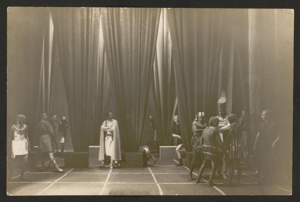 Altes Schwarz-Weiß-Foto: Theaterbühne mit 13 Schauspielern , sie tragen römisch und altägyptisch anmutende Kleidung.