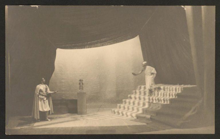 Altes Schwarz-Weiß-Foto: 2 Schauspieler auf einer Theaterbühne mit Treppe, sie tragen römisch und altägyptisch anmutende Kleidung, Statuette auf einem Podest zwischen den beiden.