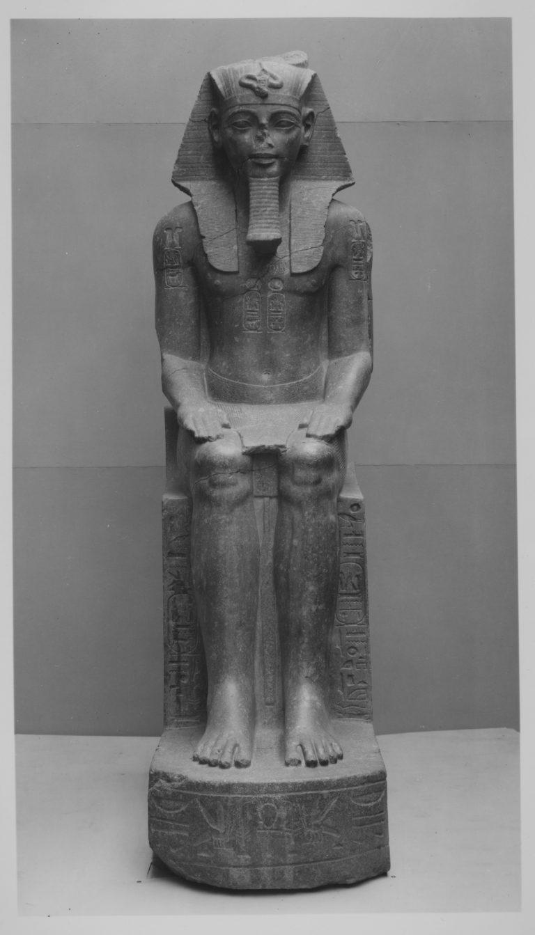 Steinerne Statue eines auf einem Thron sitzenden Pharaos. Er trägt ein Nemes-Kopftuch, den Pharaonen-Bart und einen Schurz; Auf seinen Schultern, der Brust und dem Stuhl sind Hieroglyphen eingraviert. Guter Erhaltungszustand.
