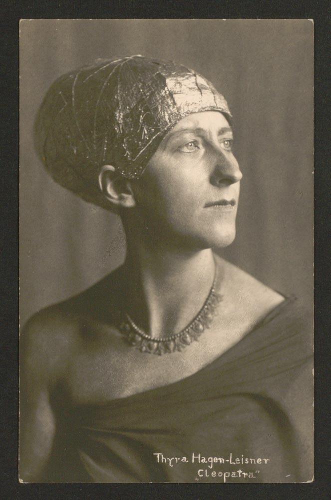 Altes Schwarz-Weiß-Foto: Frau, schaut zur Seite; Sie trägt eine enganliegende Haube, eine Kette und ein Kleid, das nur eine Schulter bedeckt.