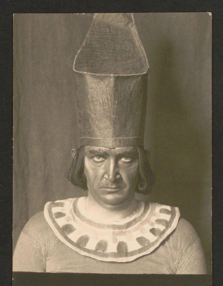 Altes Schwarz-Weiß-Foto: Mann, frontal, trägt einen altägyptischen Halskragen und die Rote Krone Unterägyptens.