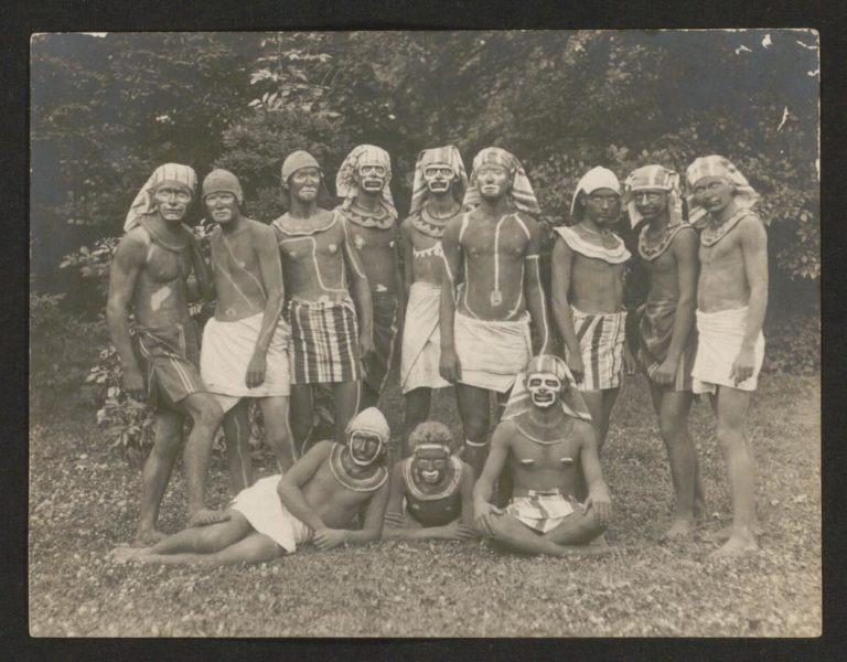 Altes Schwarz-Weiß-Foto: 12 Männer tragen die Schurze und Kopftücher; Ihre Körper und Gesichter sind mit dunkler Farbe und mit hellen Flecken und Streifen bemalt, 10 Personen von ihnen tragen einen Halskragen.