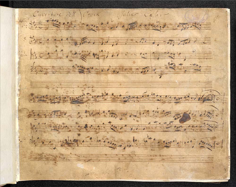 Vergilbtes und fleckiges Notenpapier; 8 Zeilen mit Noten beschriftet; Zeile 5 und 10 sind unbeschriftet; am oberen Ende mit handschriftlichem Text beschriftet.