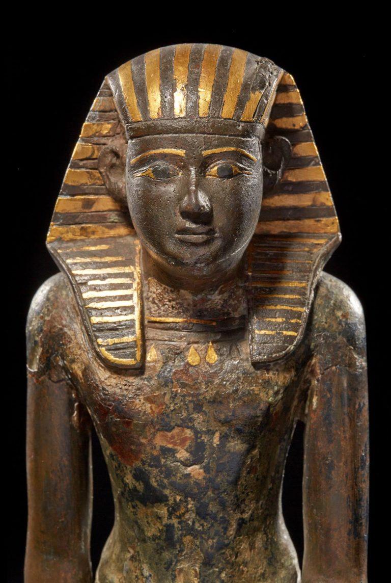 Bronzes Statuette eines Pharaos mit Goldverzierungen, frontal.; Er trägt ein gold-blaues Nemeskopftuch.