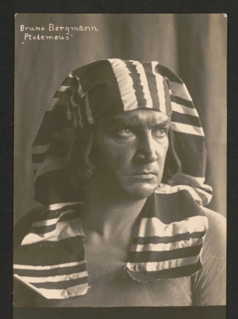 Altes Schwarz-Weiß-Foto: Mann schaut zur Seite mit einem altäyptischen Nemeskopftuch.